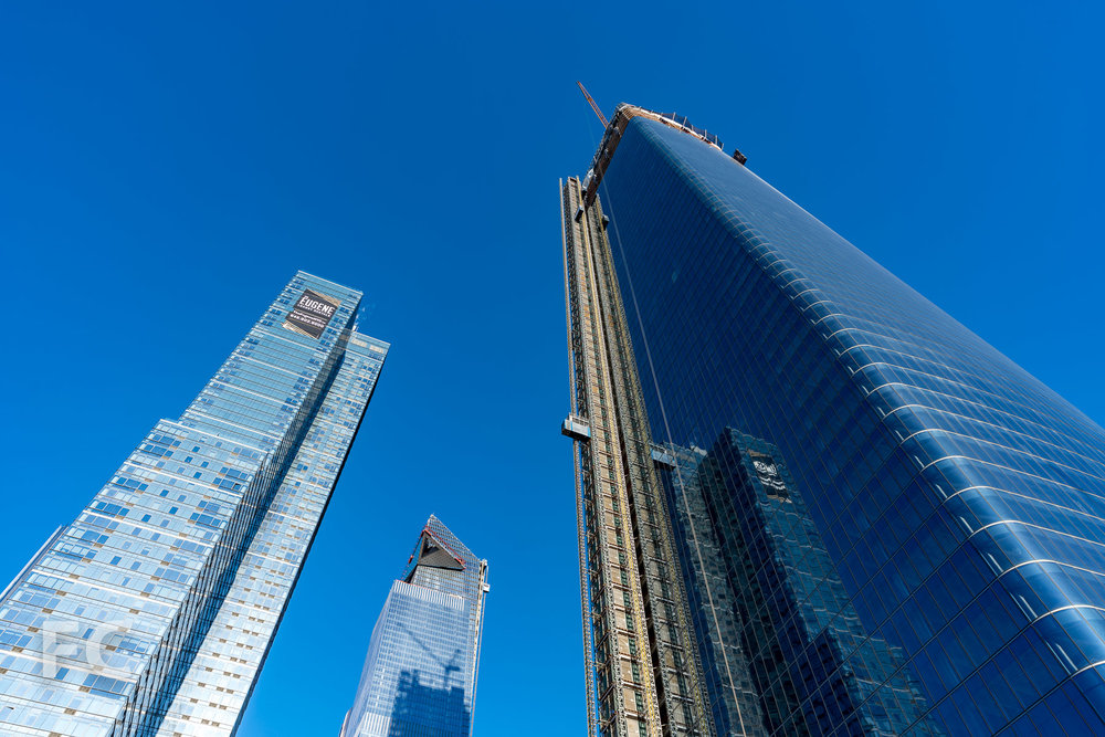 Looking up at the southeast facade of One Manhattan West (right), The Eugene at 401 West 31st Street (left), and 10 Hudson Yards (center).