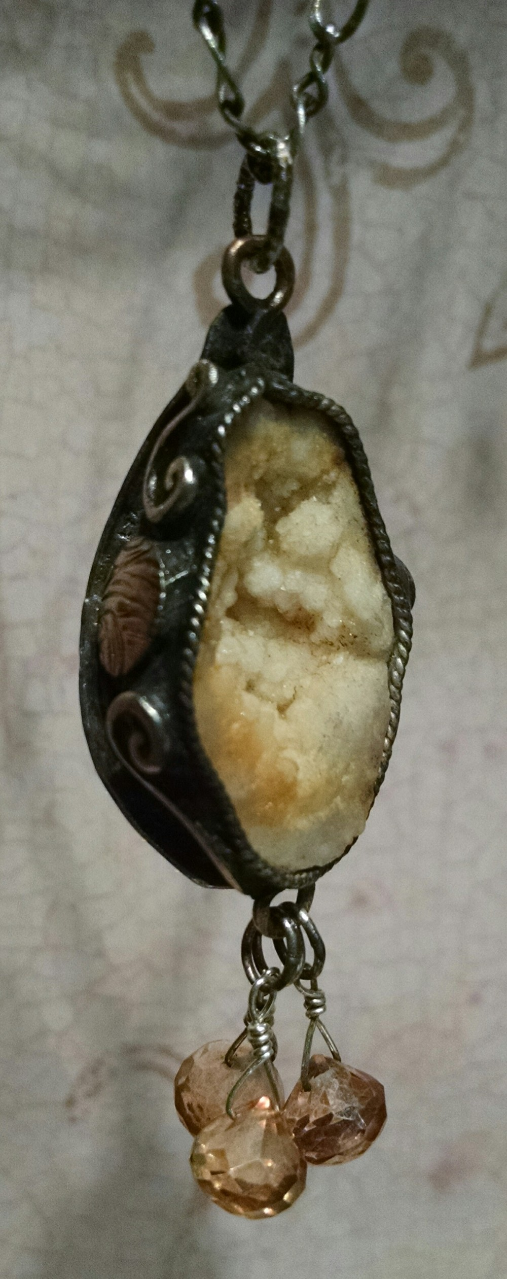 Geode mined from a private mine in Mt. Carmel fault area of Indiana. Hand-fabricated, patterned, silver-fill backing with brass details on sides. Trio of tangerine quartz