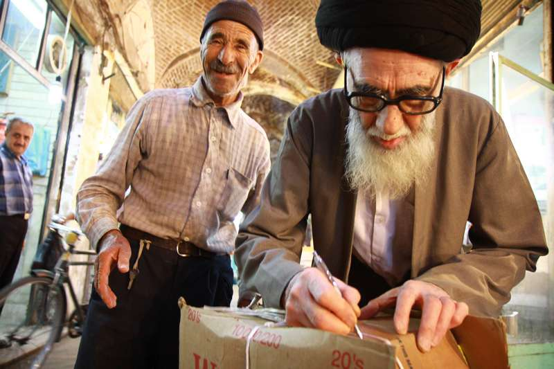 A mullah signing off a shipment of books to be transported by the man on the left.