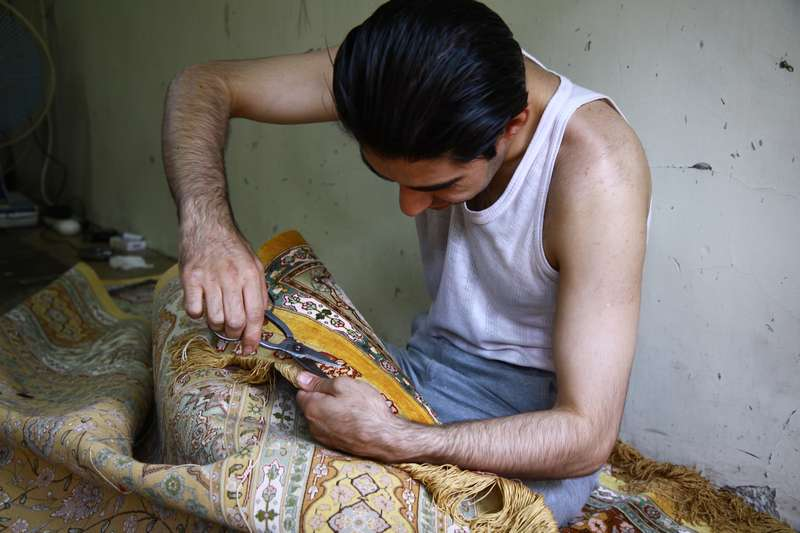 Carpet maker who may spend up to 2 years making one carpet, Tehran Iran.
