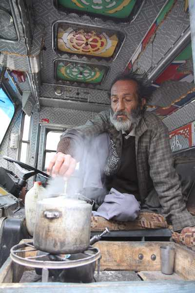 Truck driver cooking dinner in the cab of his truck on the 4 day journey to Ladakh.