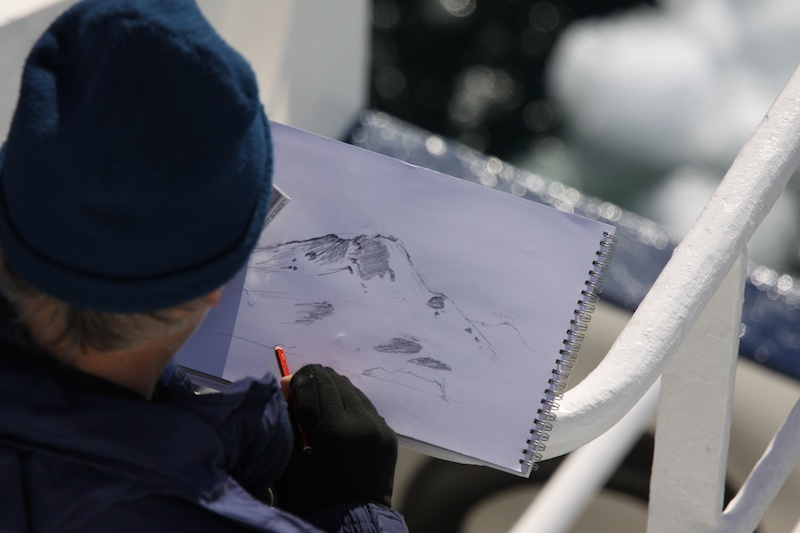 A passenger captures the majesty of Mt. Erebus on paper.