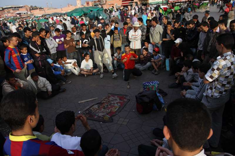 Street performers entertain a local crowd in the square in Marrakech.