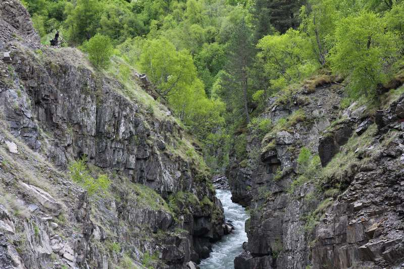 Steep cliffs and rivers dwarf us and our bikes.