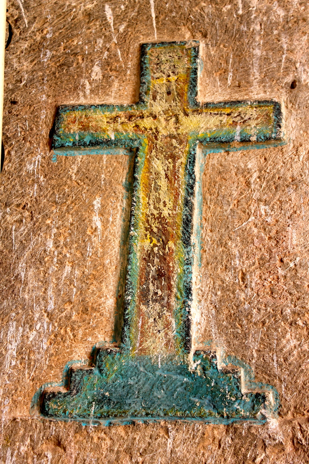 Wooden cross in stucco on a church wall in Mama (that's the name of the town, really)