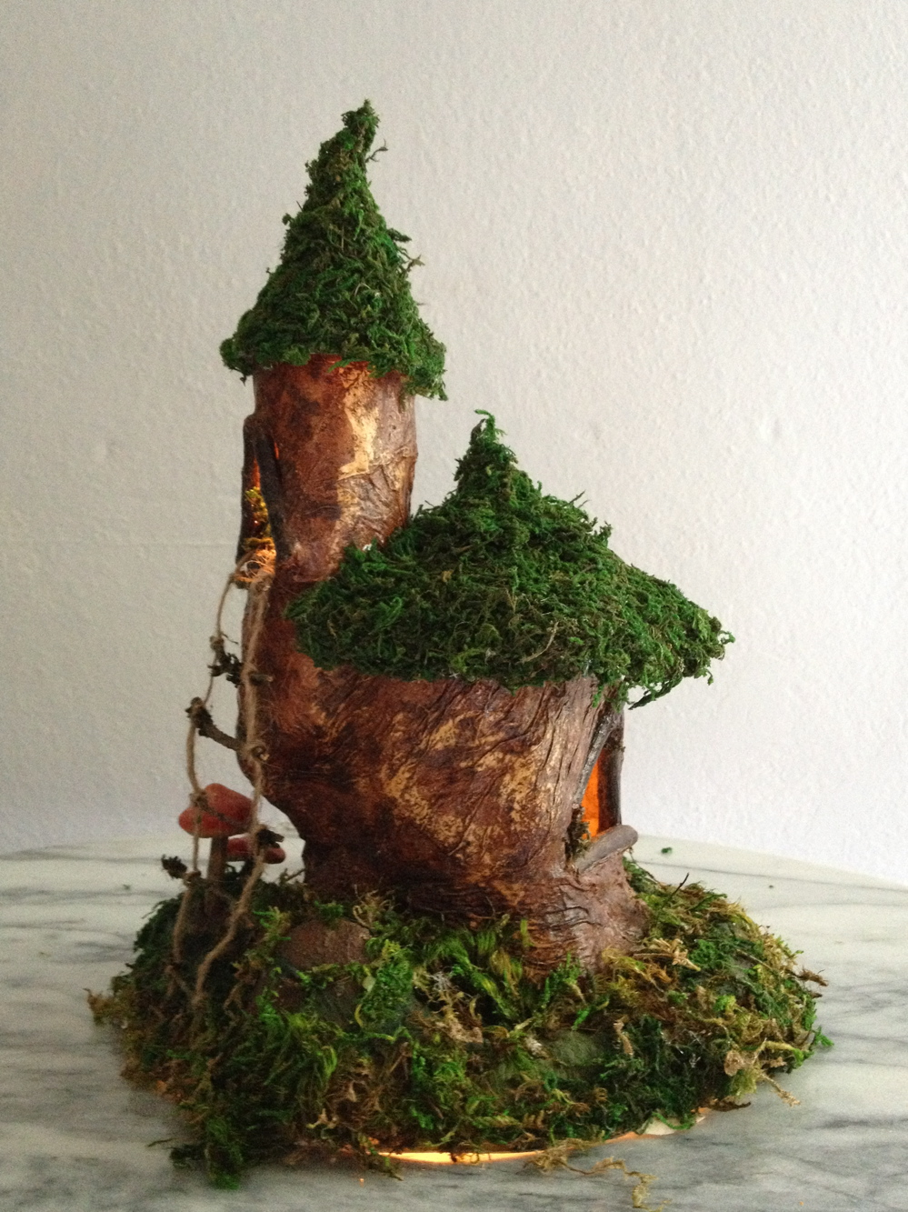 quirky handmade fairy gnome house with moss roof and mushrooms