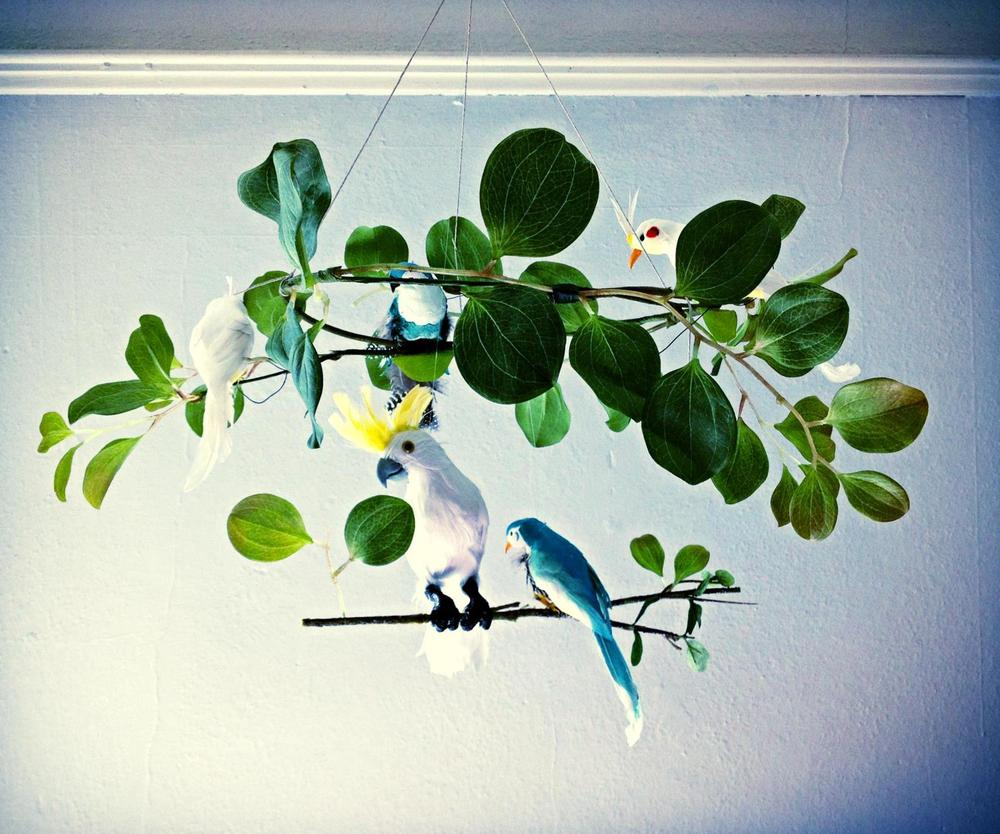 A jungle-themed baby mobile, handmade with vintage accents.