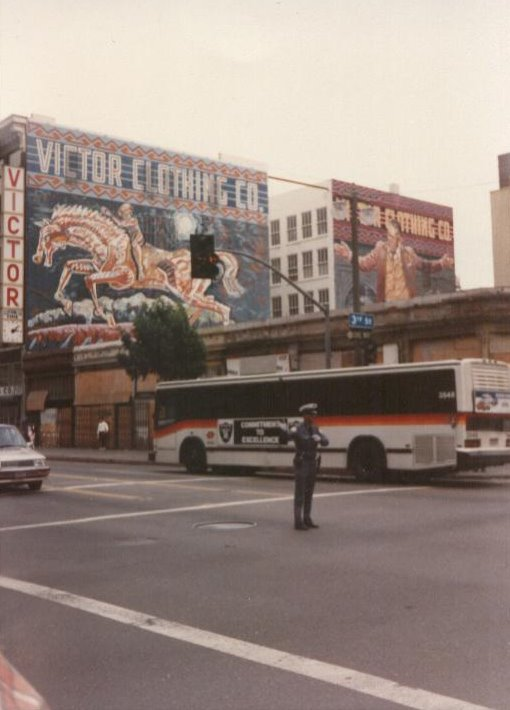 LA in 1990. This is downtown, about twenty minutes from Compton. This was the first and last tiem I saw a cop directing traffic in LA. I mean, what's going on here, there are functioning traffic lights behind him. Interesting note, you can see the LA Raiders banner on the bus, the team had just defected from Oakland.  They went back of course, and since then LA has not had an NFL team.