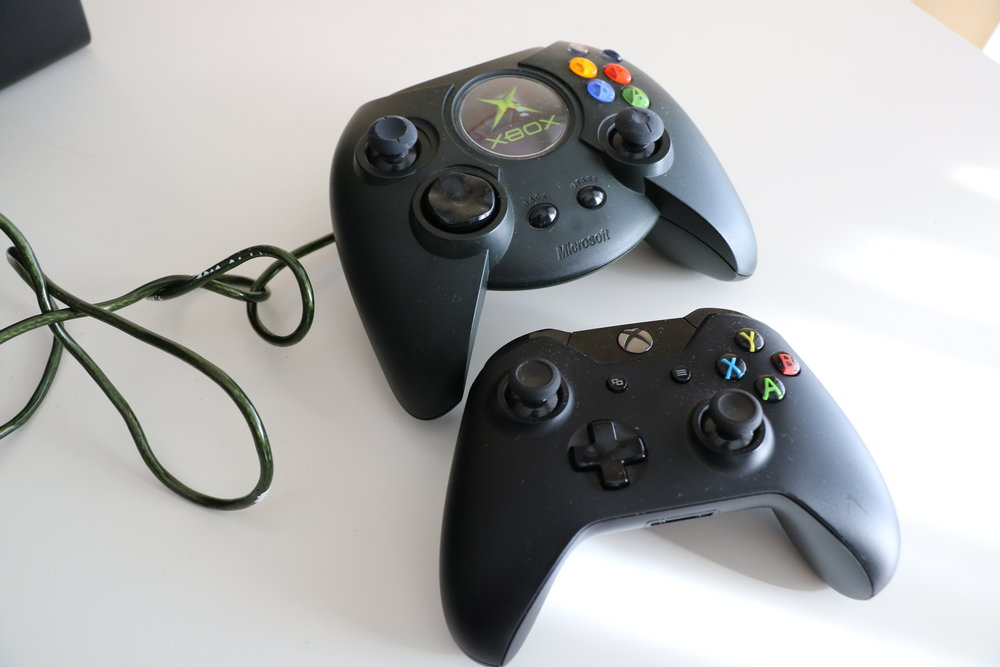"Original Xbox controller on top ""Duke"" compared to standard Xbox One controller."