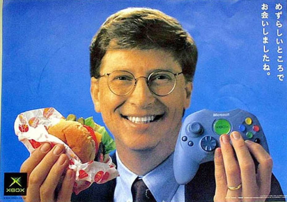 "Microsoft co-founder Bill Gates showing the Japanese launch controller, almost identical to the ""S"" version that superseeded the ""Duke"" in Western regions."