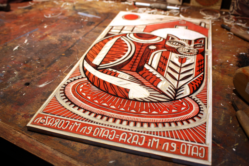 Here is the carving for the SECOND print (if you look close in the first photo you can see the FIRST carving of this block prior to printing) of this block, you must think in reverse in a few ways throughout this process, the image prints in reverse and the marks you make are actually the places where there will be no ink.  I carve these meticulously with various hand-forged Japanese style gouges and knives.  These are amazingly sharp, and rather dangerous, there is not a moment without complete concentration.  I first transferred my sketch onto the block by rubbing charcoal on the back of the original then tracing the lines.  I then refine the lines with ink and seal them so they won't print onto my proofs.  The block is stained red so I can more clearly define where marks have been made.