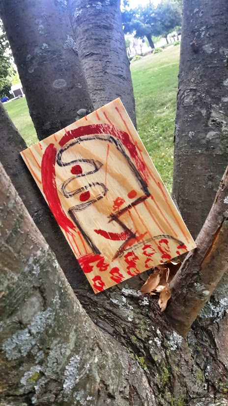 Mixed media portrait hidden in a tree. Carter Park, Leominster, MA.