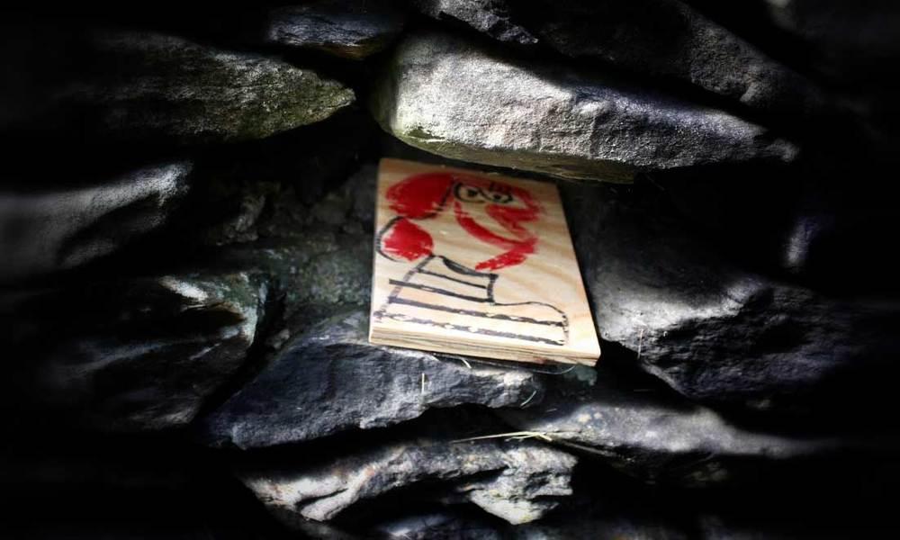 Mixed media portrait art hidden in a stone wall.