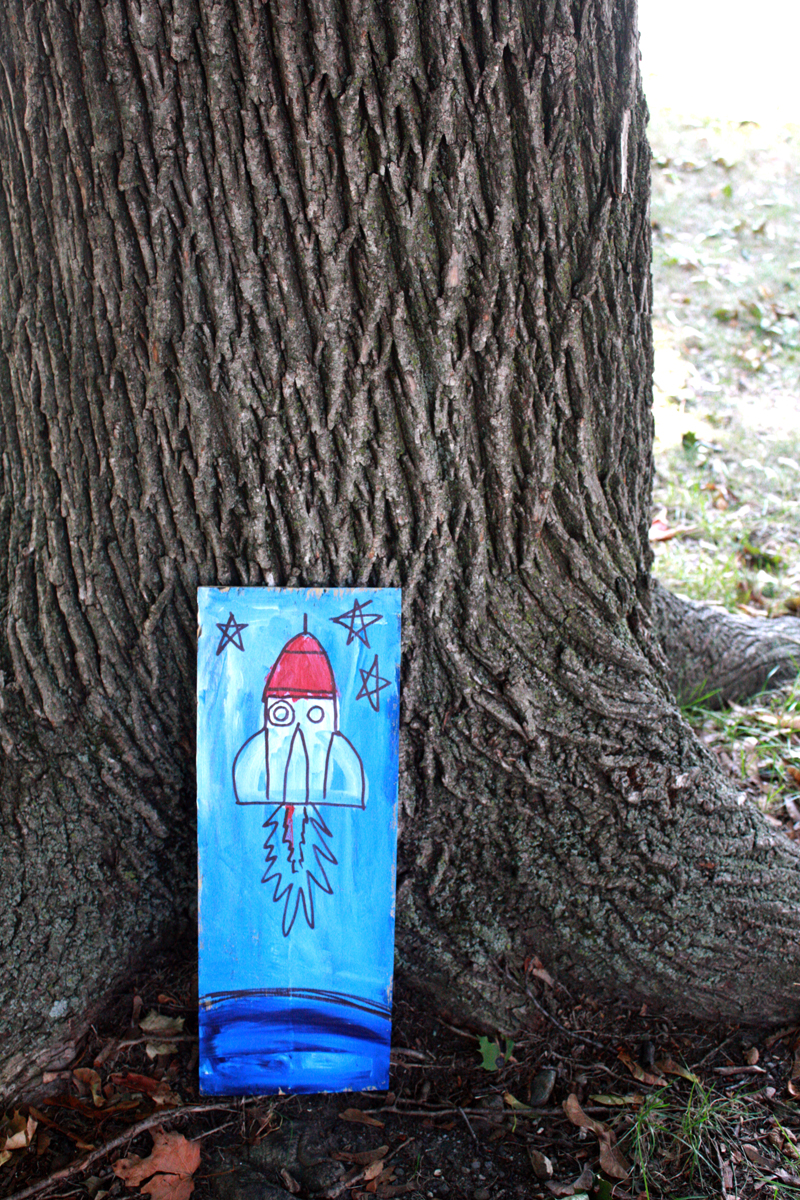 Mixed media painting of a rocket ship, against a tree in Carter Park