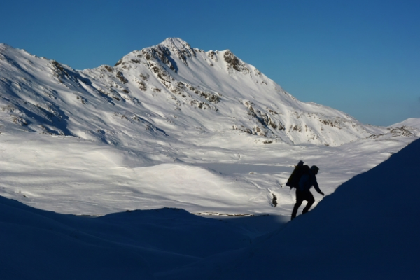 A hunter approaches a ridgeline leading to Husky Pass, on Adak Island, by Paxson Woelber