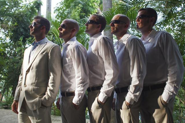 Groom and groomsmen standing sideways towards the sunlight