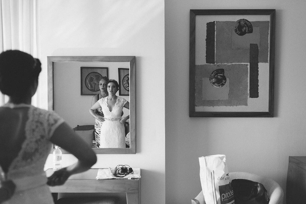 Reflejo en un espejo de la mamá de la novia ayudándole con el vestido dentro de la habitación