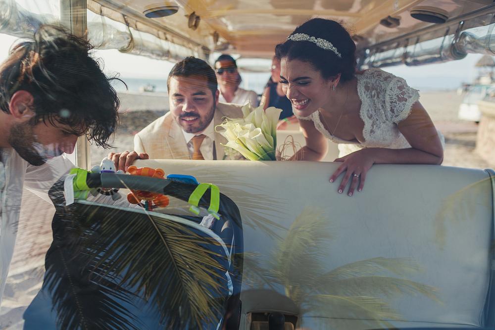 Novio y novia admirando el bebé de un invitado a bordo de un carrito de transporte en el hotel Grand Mayan en Nuevo Vallarta