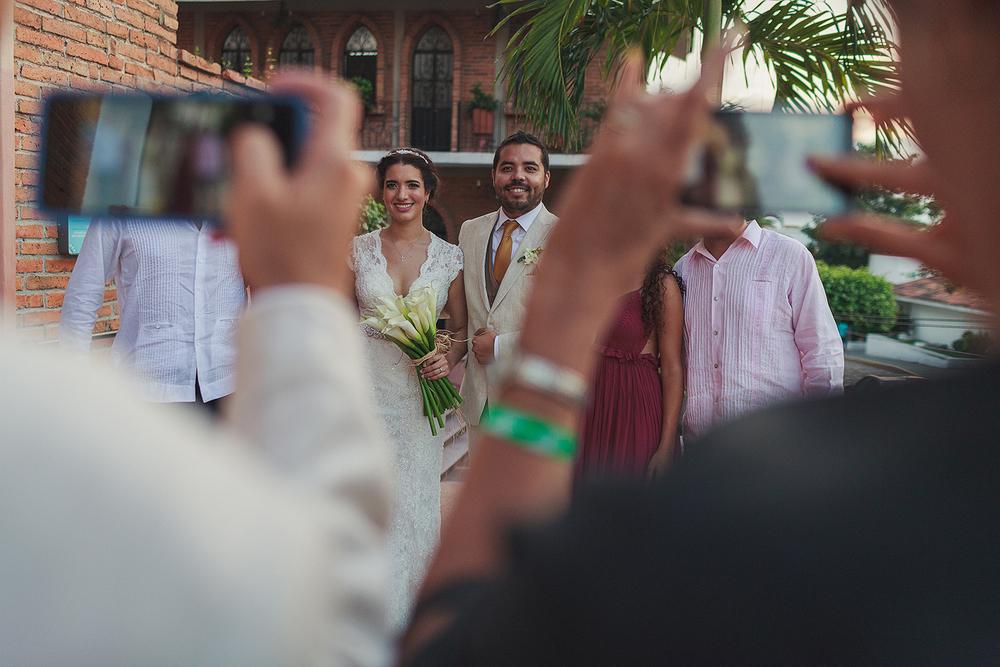 Invitados tomando fotos de los novios con otros invitados afuera de la iglesia del Refugio antes de la boda en Puerto Vallarta
