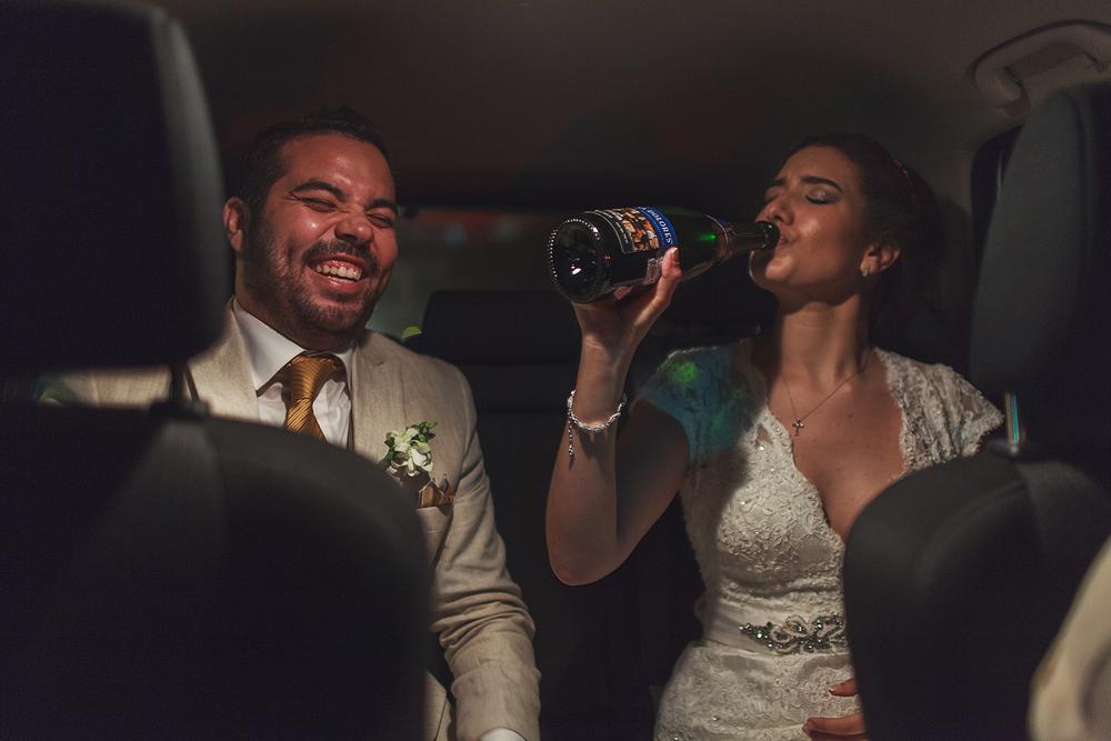 Novio ríe mientras novia bebe directo de la botella de champagne en el automóvil rumbo a la recepción de su boda en Grand Mayan Nuevo Vallarta