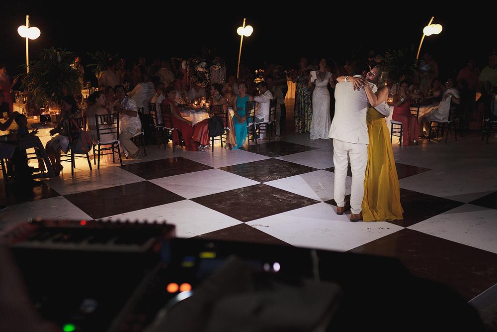 Abrazo entre mamá y novio al terminar su baile, invitados sentados en sus mesas apreciando el momento