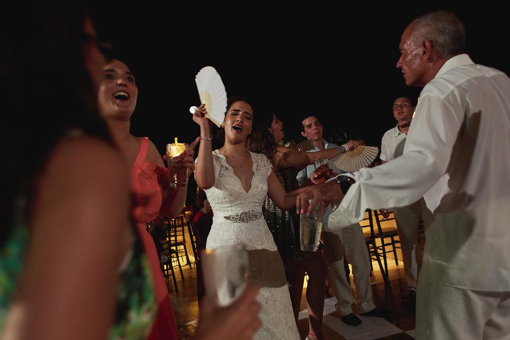 Novia disfrutando la fiesta con invitados, sostiene un abanico por el calor