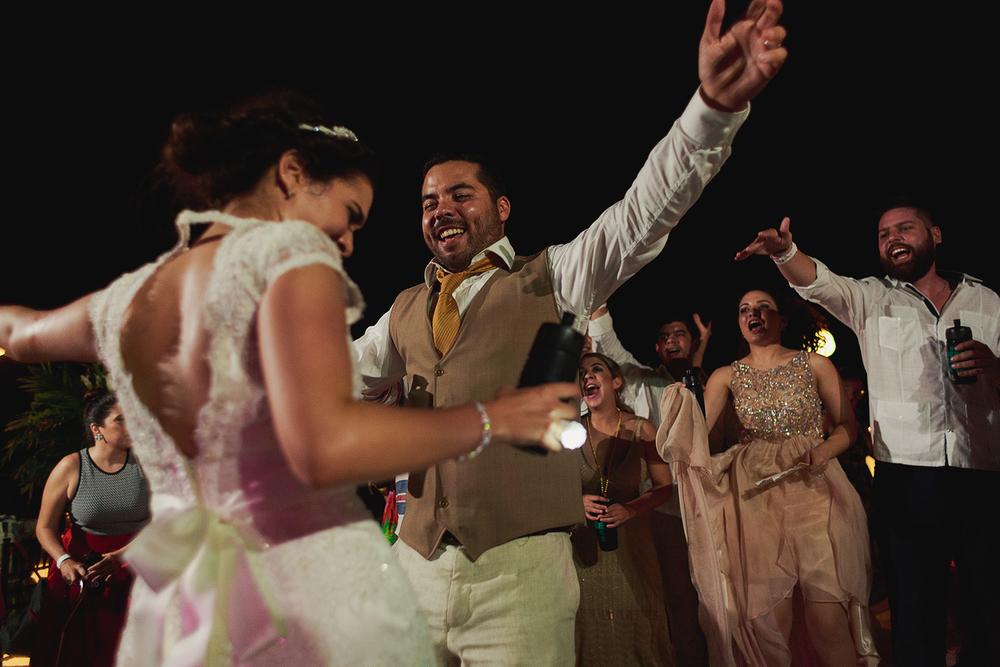 Novio y novia bailando en la pista mientras invitados los animan durante la recepción de su boda en Grand Mayan Nuevo Vallarta