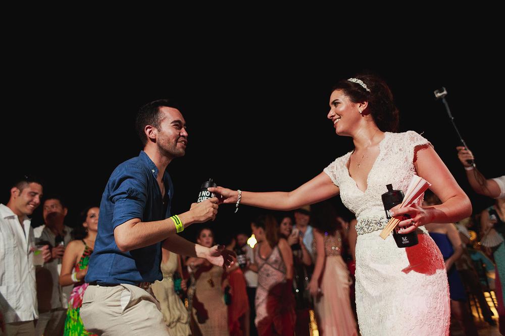 """Novia bailando con invitado en medio de """"la rueda"""", ambos sostienen cilindros de plástico con bebidas"""