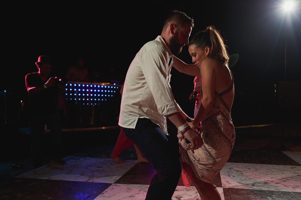 """Pareja de invitados bailando """"pegadito"""" casi al terminar la fiesta del día de la boda"""