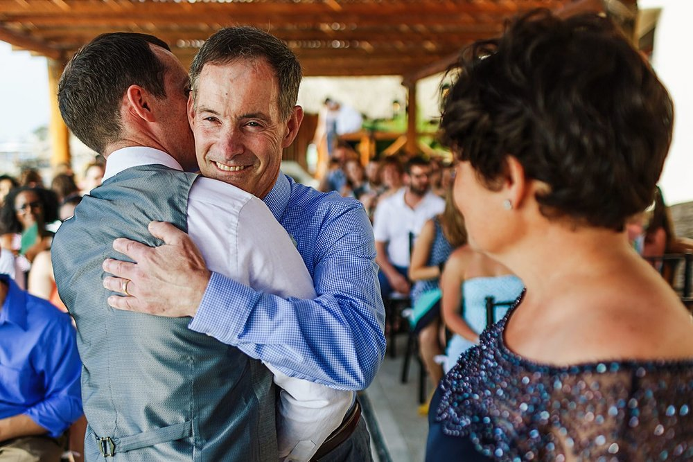 Father hugs groom at the end of the aisle, mom can be seen in foreground