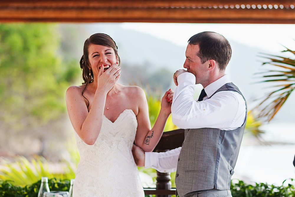 Bride laughs at groom after their first kiss while groom wipes lipstick off his lips