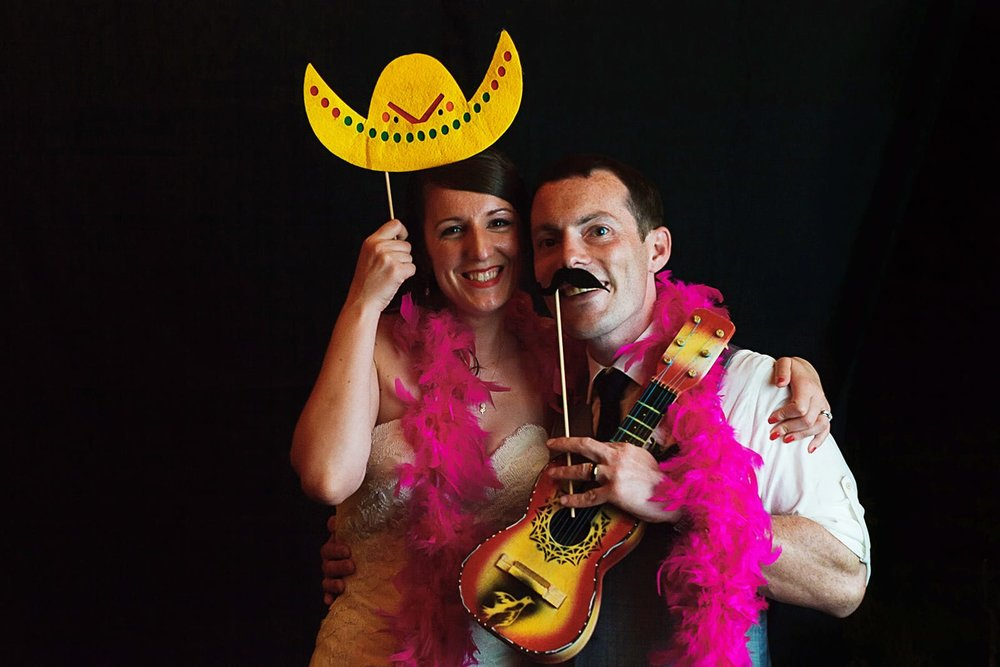 Bride and groom wear a feather boa, fake mustache and sombrero on the photo booth