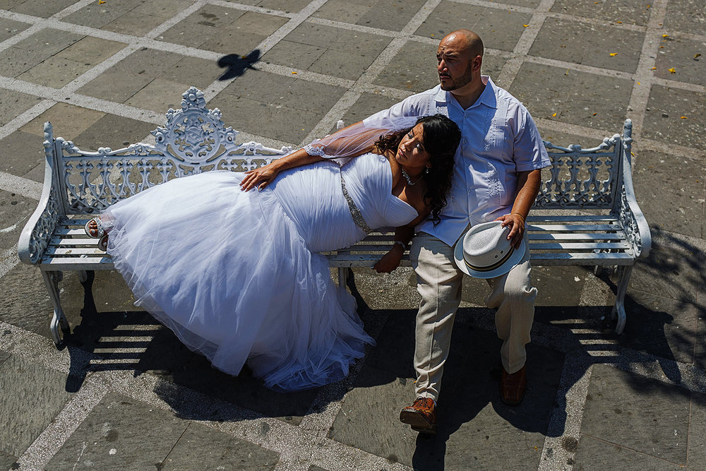 Groom sitting down in a white bench at the main square of Puerto Vallarta, bride is laying on him while a pigeon pass-by