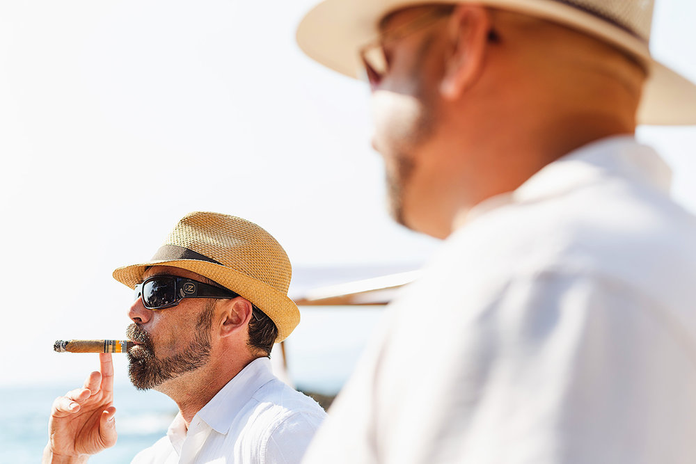 Guests smoke a cigar before the ceremony on the beach begins
