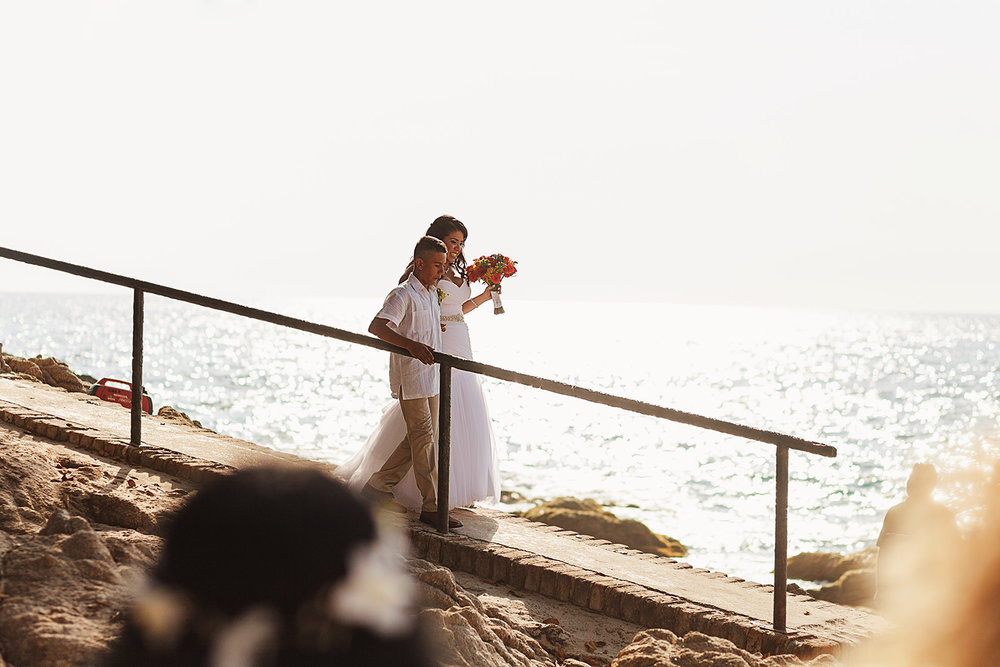 Bride and her son walking down a ramp to get to the beach ceremony