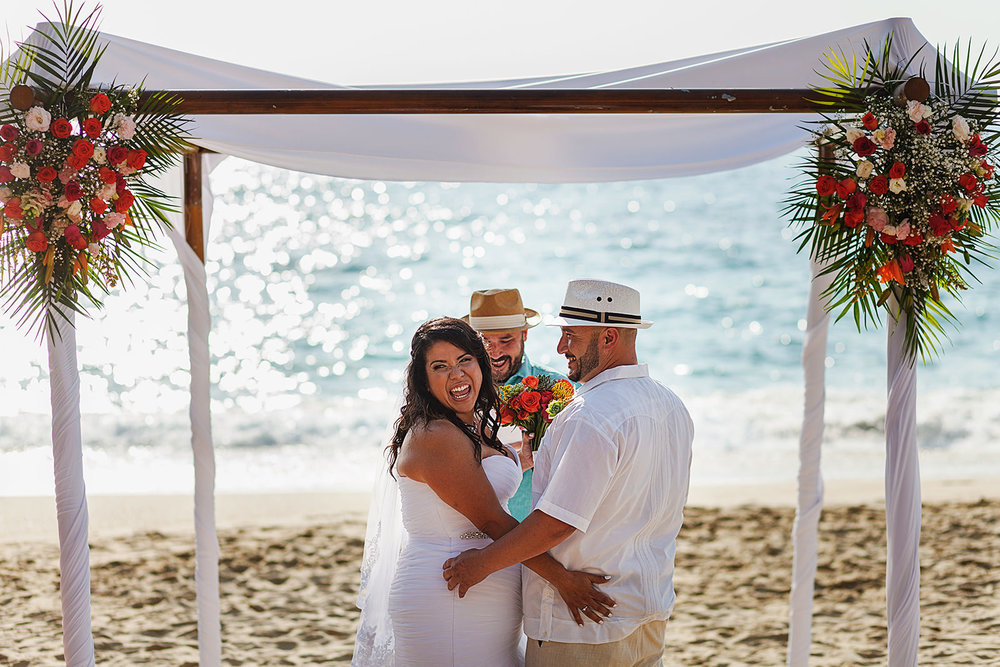 Bride turns at guests during her beach wedding ceremony