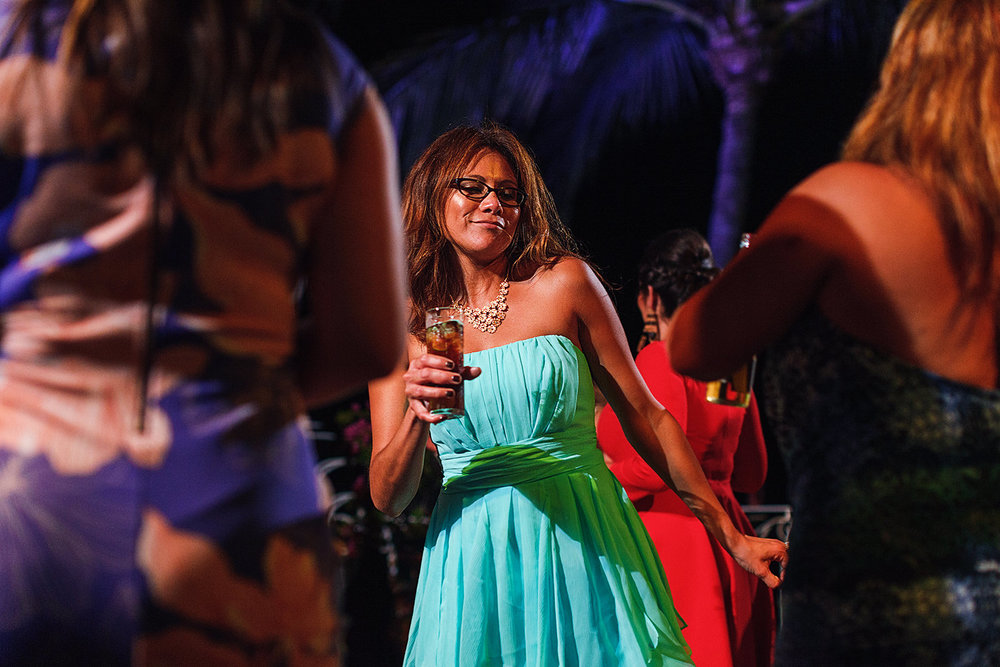bridesmaid holding a drink and dancing with guests at wedding reception