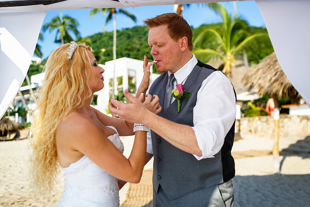 bride and groom feed cake at each other after ceremony on the beach