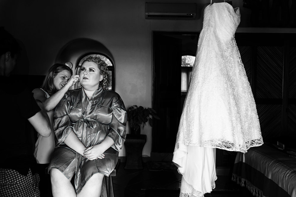 bride getting ready next to her hanging wedding dress