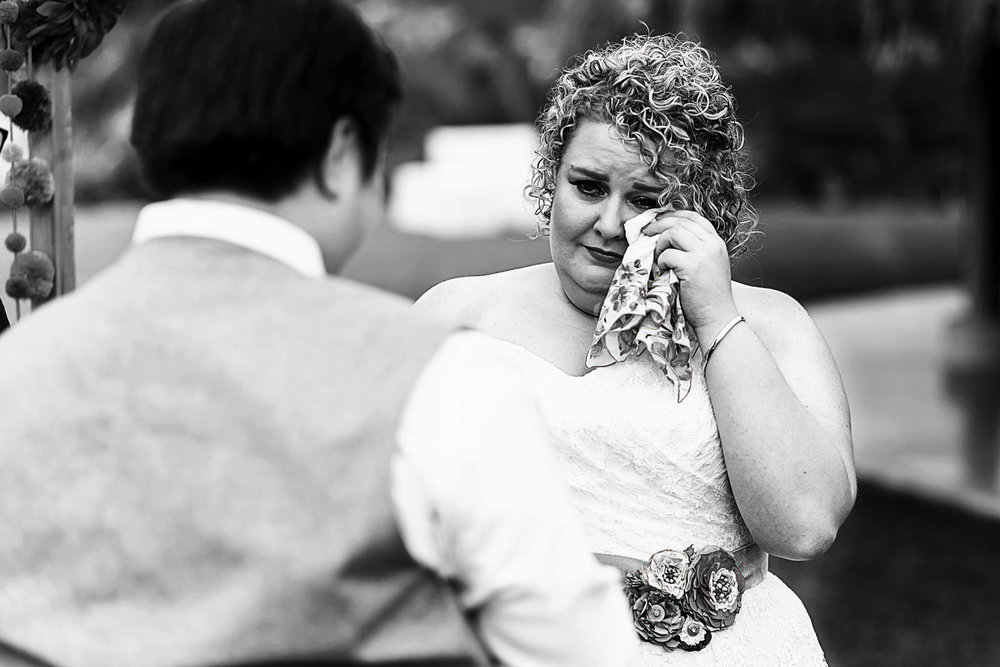Bride wiping tear with handkerchief at wedding ceremony