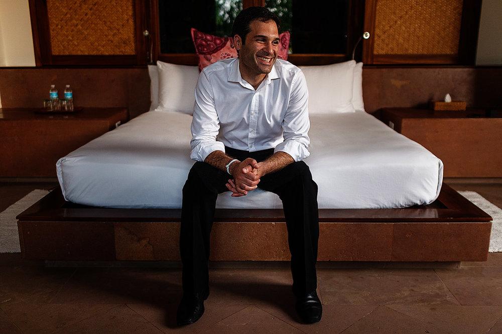Young man sitting at the edge of a bed in a room at Imanta Resort, Punta Mita