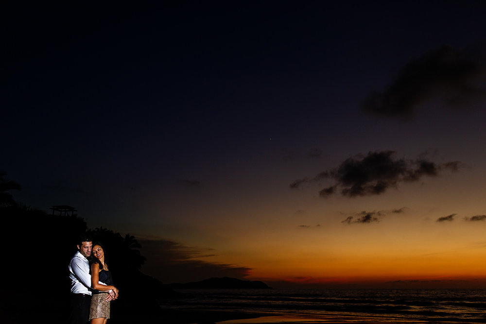 Couple standing on the beach under dramatic