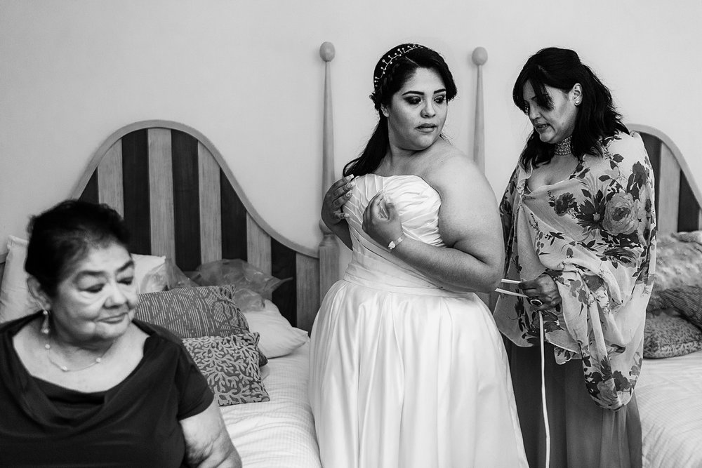 Mom helping bride putting her wedding dress on before the ceremony