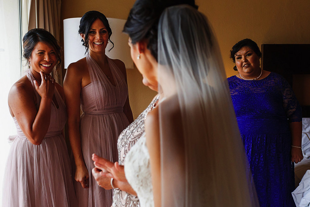 Bridesmaids and maid of honor react at bride all ready to go