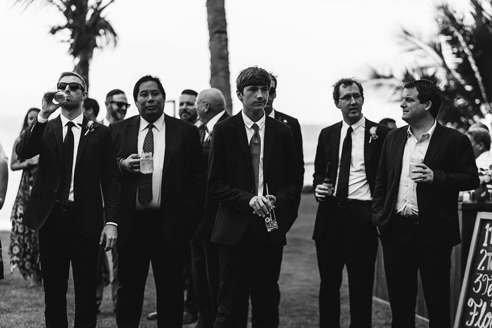 black and white photo of groomsmen in suit holding drinks at reception