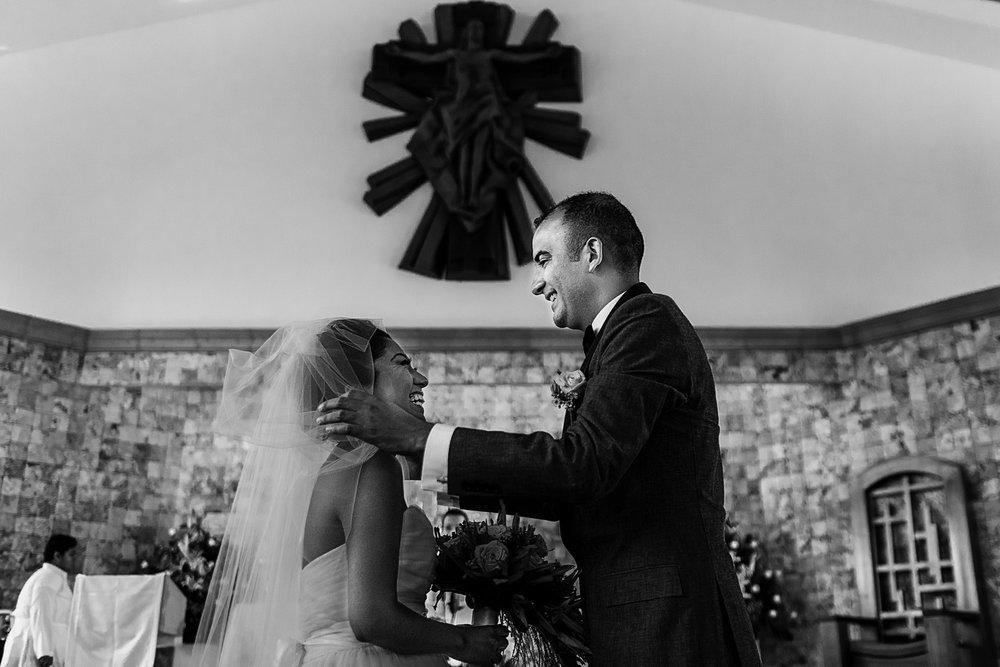 Novio removiendo el velo de la cara de su prometida al comenzar la ceremonia de boda