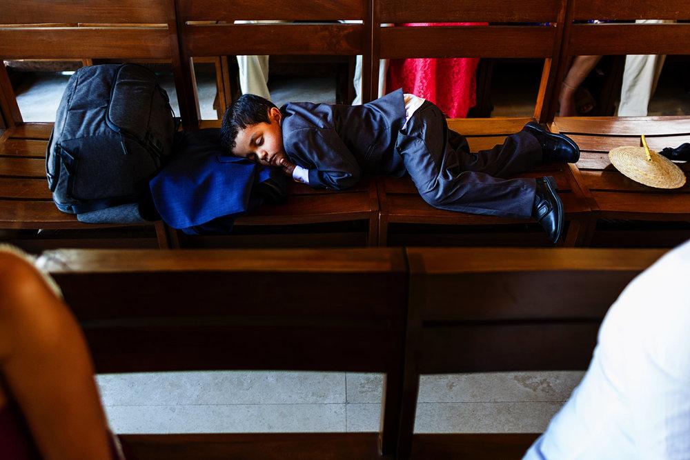 Niño dormido en banca de la iglesia