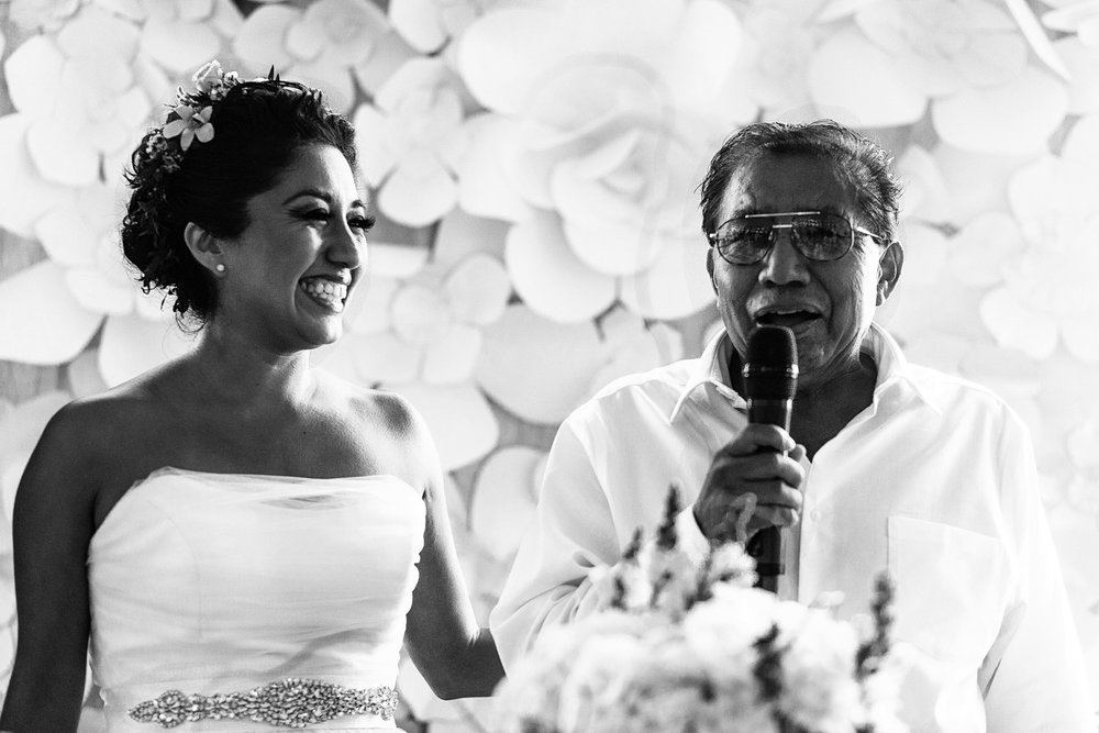 Papá de la novia dando un brindis, la novia sonríe a su lado
