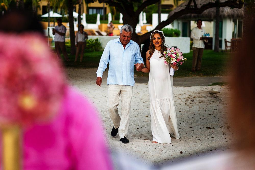 Papá y novia caminando hacia el altar durante ceremonia de boda destino en la playa