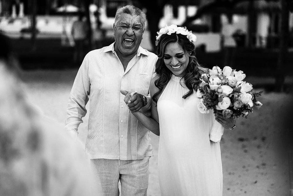 Papá de la novia carcajeando mientras camina hacia la boda